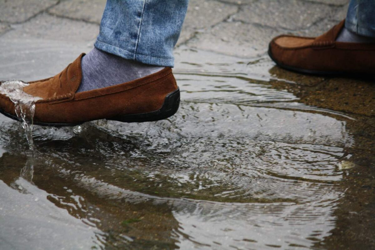 GoGonano coated shoes in rain walking through dirt pool